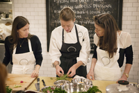 Portrait of female chef teaching two students in commercial kitchen