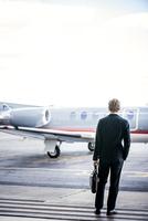 Rear view of businessman looking at jet 11100013193| 写真素材・ストックフォト・画像・イラスト素材|アマナイメージズ