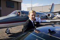 Portrait of businessman getting into car on airport runway with corporate jet in background 11100013197| 写真素材・ストックフォト・画像・イラスト素材|アマナイメージズ