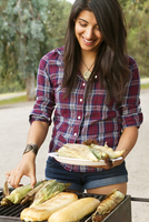 Young woman grilling corn