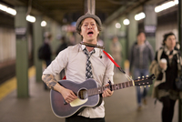 Portrait of musician playing acoustic guitar and singing in subway station