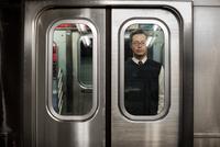 Portrait of man looking through door glass of subway train
