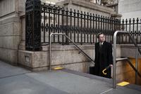 Businessman with umbrella and suitcase on sidewalk