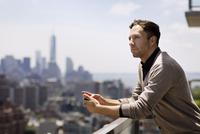 Man on balcony looking at view 11100014185| 写真素材・ストックフォト・画像・イラスト素材|アマナイメージズ