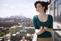 Woman on balcony looking at view 11100014191| 写真素材・ストックフォト・画像・イラスト素材|アマナイメージズ