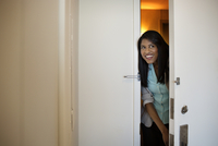 Woman peeking through front door of apartment