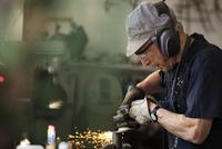 Senior artist creating metal sculpture in studio
