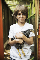 Portrait of boy (8-9) holding chicken