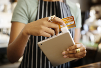 Close-up of waitress holding digital tablet and credit card
