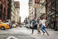 Three women running on street
