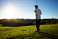 Man watching drive on golf course