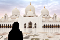 Woman in burka against mosque