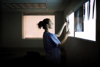 Doctor looking at x-ray image 11100017275| 写真素材・ストックフォト・画像・イラスト素材|アマナイメージズ