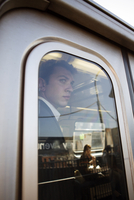 Young businessman standing inside train
