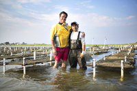 Oyster fishermen standing in waders