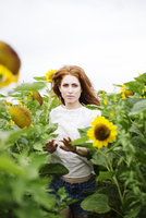 Portrait of mid-adult woman standing in sunflower field