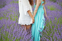 Two women holding hands in field of lavender