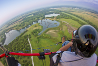 Fish-eye view of paragliding over farmland