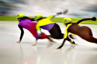 Three female speed skaters rounding track curve during race