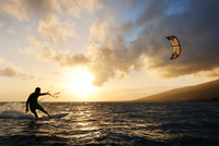 Man kiteboarding at sun set