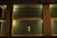Young woman standing outside motel in nightgown