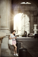 Young woman leaning on building column using smart phone