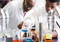 Teacher and schoolboy (14-15) in school laboratory