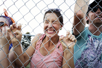 Woman holding at chain link fence and clenching teeth at baseball game