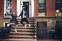 Couple in formal wear jumping from steps