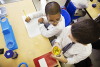 Schoolboys learning in classroom during chemistry lesson