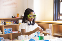 Portrait of schoolgirl (6-7) in classroom wearing safety goggles pouring liquid from beaker to test tube