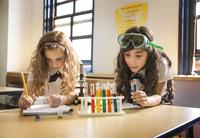 Schoolgirls (8-9) working on science experiment in class