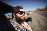 Bearded man in sunglasses looking out through car window road in background