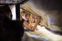 Girl (6-7) face to face with cat under bed