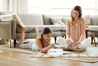 Girl (10-11) doing homework with her mom