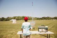 Young boy (12-13) launching model rocket