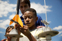 Man launching model rocket with kids (8-9)