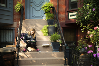 Teenage girl using digital tablet on doorsteps