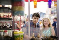 Teenage couple (14-15, 16-17) at amusement park buying sweets 11100022113| 写真素材・ストックフォト・画像・イラスト素材|アマナイメージズ