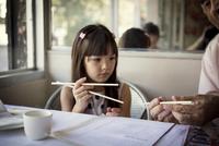 Grandfather teaching granddaughter (6-7) to use chopsticks