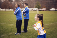 Girl (8-9) shouting,  trainers watching,  soccer practice