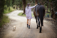 Young woman walking with dog and horse