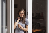 Woman standing with coffee in window