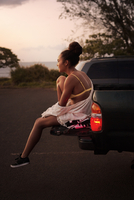 Teenage girl (16-17) undressing in parking lot by sea
