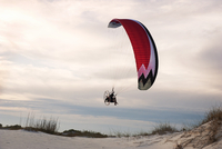 Man paragliding over beach