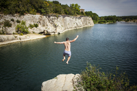 Young man jumping into river
