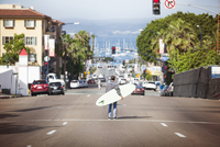 Man with surfboard in middle of street