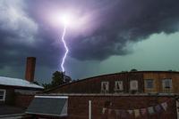 Lightning striking behind houses
