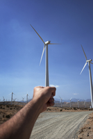 Forced perspective of hand holding wind turbine