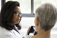 Doctor talking to patient,  using digital tablet